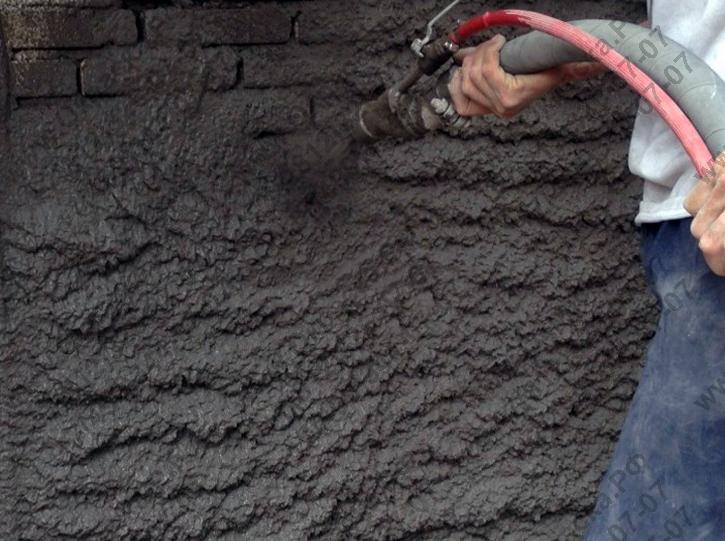 Распыление штукатурки на стены с помощью машины для штукатурки.